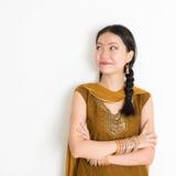 Mixed race Indian girl in sari dress. Portrait of arms crossed mixed race Indian Chinese girl in traditional Punjabi dress looking side upward, standing on plain Royalty Free Stock Photography
