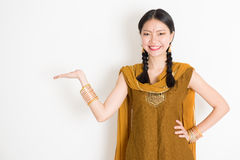 Mixed race Indian girl showing something. Portrait of young mixed race Indian Chinese female in traditional punjabi dress hand holding somethings, standing on Stock Photography