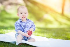 Mixed Race Infant Baby Boy Sitting on Blanket Holding Apple Outs stock images