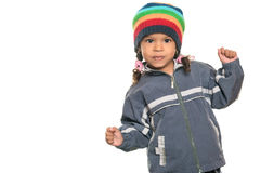 Mixed race little girl with a funny attitude. Wearing a colorful beanie hat and a jacket isolated on white royalty free stock image