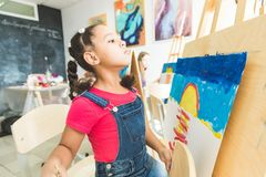 Mixed race little girl with a teacher in group of preschool student sat the drawing a picture. Painting on maelbert royalty free stock images