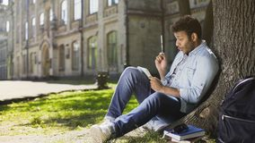 Mixed-race male sitting under tree, writing in sketchbook, innovative idea royalty free stock photo