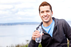 Mixed race man holding water bottle royalty free stock images