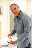 Mixed race man ironing Stock Photos