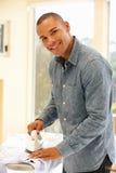 Mixed race man ironing Stock Photos