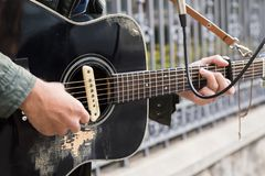 A mixed race man playing guitar in the street royalty free stock images