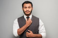 Mixed race man straightening his tie Stock Photography