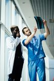 Mixed race medical doctors. Two male doctors reviewing x-ray in hospital corridor stock photography