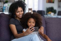 Mixed-race mom and child girl making video call on cellphone. Happy smiling african american mother and little daughter taking selfie on smartphone, mixed race royalty free stock photos