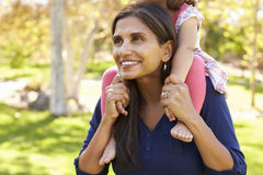 Mixed race mother carrying young daughter on shoulders, crop Royalty Free Stock Photography