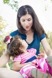 Mixed Race Mother and Cute Baby Daughter Playing with Cell Phone. In Park royalty free stock photo