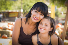 Mixed Race Mother and Daughter Portrait at the Pumpkin Patch. Attractive Mother and Baby Daughter Portrait in a Rustic Ranch Setting at the Pumpkin Patch Stock Photo