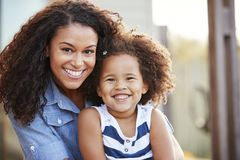 Mixed race mother and young daughter smile to camera outside stock images