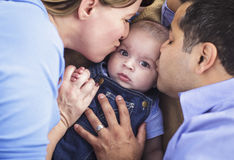 Mixed Race Parent Kissing Their Son. Together Stock Image