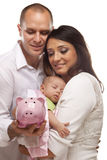 Mixed Race Parents with Baby Holding Piggy Bank. Attractive Young Mixed Race Parents with Baby Holding Piggy Bank on a White Background Stock Images