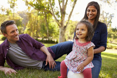 Mixed race parents and young daughter sit in park, close up Stock Photos