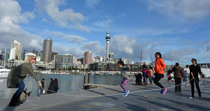 Mixed race people jumps on a rope in  Wynyard Quarter against  A Royalty Free Stock Photo