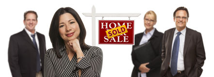 Mixed Race People with Sold Real Estate Sign Isolated. Pretty Hispanic Woman and Other People Behind in Front of Sold Home For Sale Real Estate Sign Isolated on Royalty Free Stock Photography
