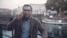 Middle Eastern young man in a European city talking on the phone. Mixed race person young man in a European city talking on the phone stock footage