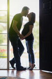 Mixed Race Pregnant Couple Kissing in Doorway. Loving Mixed Race Pregnant Couple Kissing in Doorway stock photography