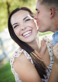 Mixed Race Romantic Couple Whispering in the Park Royalty Free Stock Image