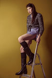 Mixed race fashion model posing on stepladder. Royalty Free Stock Photo