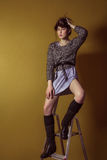 Mixed race fashion model posing on stepladder. Royalty Free Stock Images