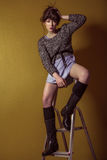 Mixed race fashion model posing on stepladder. Stock Images