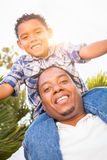 Mixed Race Son and African American Father Play Piggyback Out. Mixed Race Son and African American Father Playing Piggyback Outdoors Together Stock Image