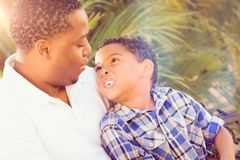 Mixed Race Son and African American Father Talking Outdoors. Mixed Race Son and African American Father Playing Outdoors Together Stock Photography