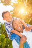 Mixed Race Son and African American Father Playing Piggyback Out. Mixed Race Son and African American Father Playing Piggy-back Outdoors Together Royalty Free Stock Photos