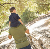 Mixed Race Son Enjoys a Piggy Back in the Park with Dad Royalty Free Stock Image