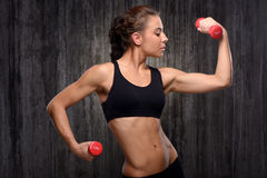 Mixed race sporty woman holding dumbbells Royalty Free Stock Image