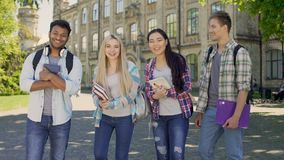 Mixed-race students laughing looking into camera, standing on university campus. Stock footage stock footage