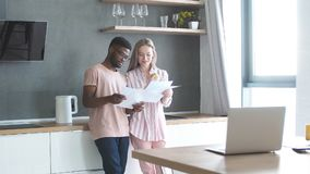 Mixed-race students standing together on kitchen at home prepare to exams stock footage