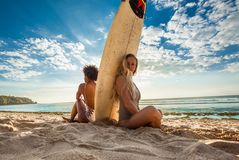 Mixed race surfer girls sitting back to back with surfboard in between. In front of a breathtaking seascape on summer day, watching waves at beautiful Padang Royalty Free Stock Photography