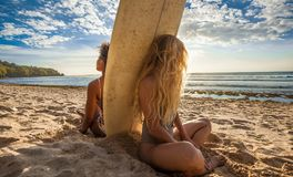 Mixed race surfer girls sitting back to back with surfboard in between. In front of a breathtaking seascape on summer day, watching waves at beautiful Padang Stock Images