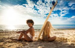 Mixed race surfer girls sitting back to back with surfboard in between stock photos