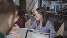 Mixed race team working together on architectural design in modern co-working space. Group of people talking. stock video footage