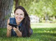 Mixed Race Teen Female Texting on Cell Phone Outside. Attractive Happy Mixed Race Young Female Texting on Her Cell Phone Outside Laying in the Grass Royalty Free Stock Image