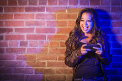 Mixed Race Teen Using Her Cell Phone Against Brick Wall Royalty Free Stock Photography