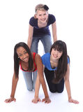 Mixed race teenage girl friends in fun pyramid stock photography