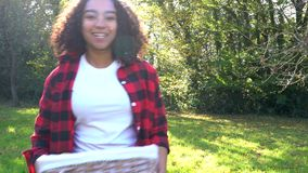 Mixed race teenage girl young woman carrying basket of apples past a gray tractor through a sunny apple orchard stock video footage