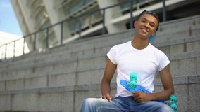 Mixed-race teenager with skateboard smiling into camera, leisure activity, hobby. Stock footage stock video