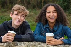 Mixed Race Teenagers Boy & African American Girl Drinking Coffee. Mixed race group of two happy children teenagers, African American girl, caucasian boy leaning stock photography