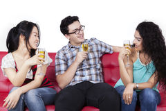 Mixed race teenagers drinking beer. Joyful multi ethnic people sitting on couch while drinking beer together, isolated on white background Stock Photo