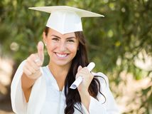 Mixed Race Teen Girl Gives Thumbs Up at Graduation In Cap and Gown. Mixed Race Thumbs Up Girl Celebrating Graduation Outside In Cap and Gown with Diploma in Hand royalty free stock photo