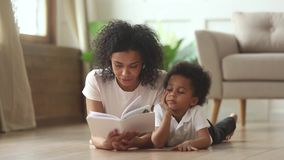 African son lying on floor with mother reading fairytale story