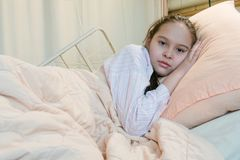 Mixed race tween girl in hospital bed, looking at camera Royalty Free Stock Images