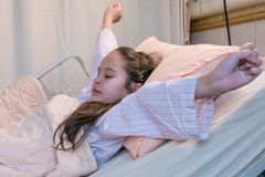 Mixed race tween girl in hospital bed, stretching Stock Photos